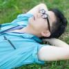 休憩中、芝生で空を眺める青い作業着姿の男性