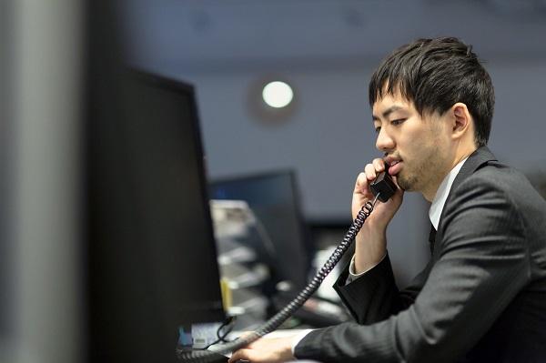 取引先に電話を掛けるオフィスのサラリーマン